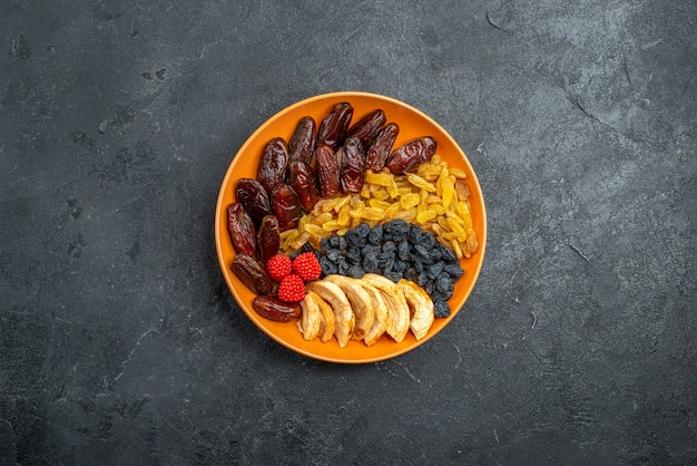 Top view dried fruits with raisins inside plate on grey space
