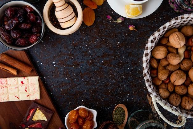 Vista dall'alto di frutta secca con noci, barrette di cioccolato e spezie su fondo nero con copia spazio