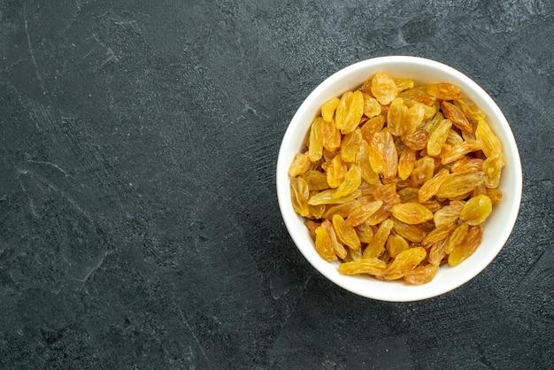 Top view dried grape raisins inside white plate on dark surface raisin fruit dried sour