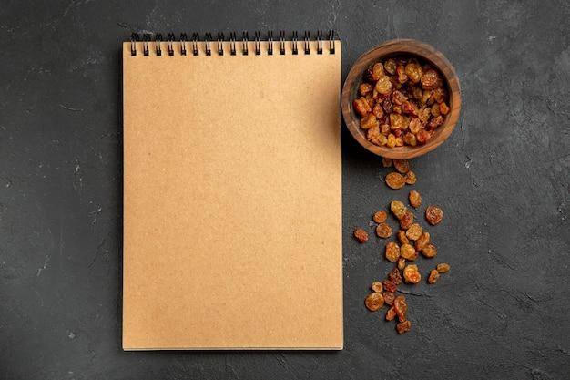 Top view dried grape raisins with notepad on dark surface dry fruit raisin