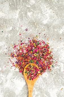 Vista dall'alto di piccoli fiori secchi polvere come colorato sul cucchiaio di legno sulla superficie bianca fiore pianta albero polvere