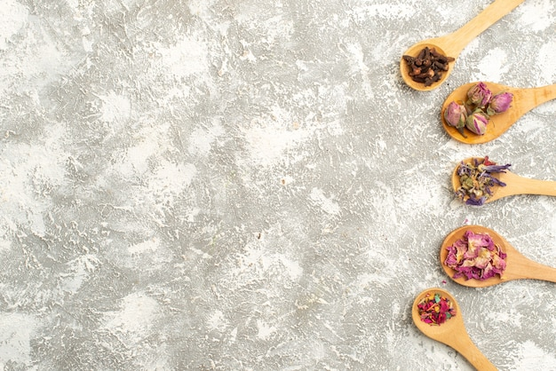 Вид сверху сушеные маленькие цветы на деревянных ложках на белом фоне цветок завод дерево пыль