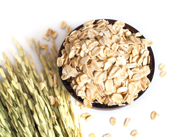 Top view of dried oatmeal, rolled oats in wooden bowl with dry grains and ear of rice isolated