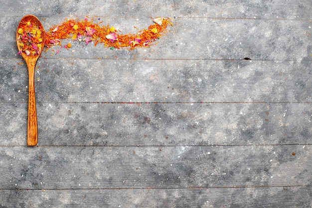 灰色の素朴な空間に木のスプーンの中の上面図乾燥オレンジ色の花