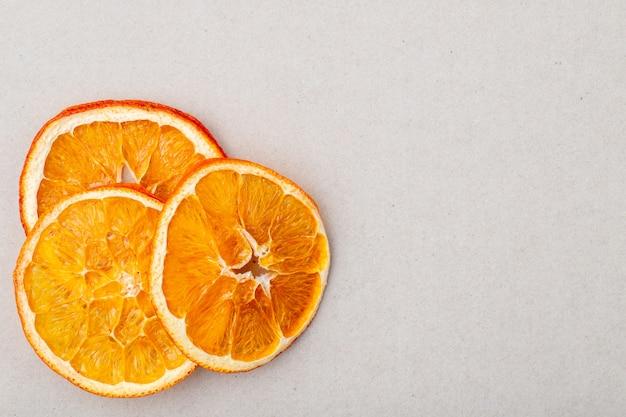 La vista superiore delle fette arancio secche ha sistemato su fondo bianco con lo spazio della copia