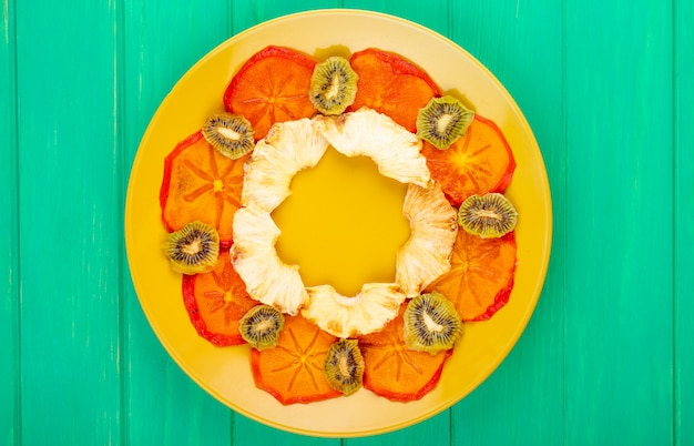 Top view of dried persimmon slices with pineapple and kiwi slices arranged on a yellow plate on green wooden background