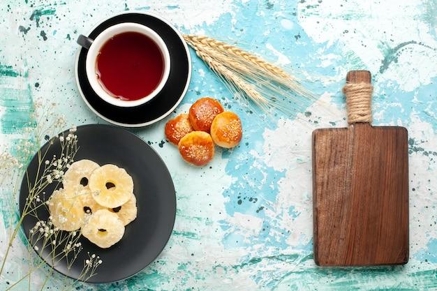밝은 파란색 배경 과일 파인애플 건조 달콤한 설탕에 케이크와 차 한잔과 함께 접시 안에 상위 뷰 말린 파인애플 링