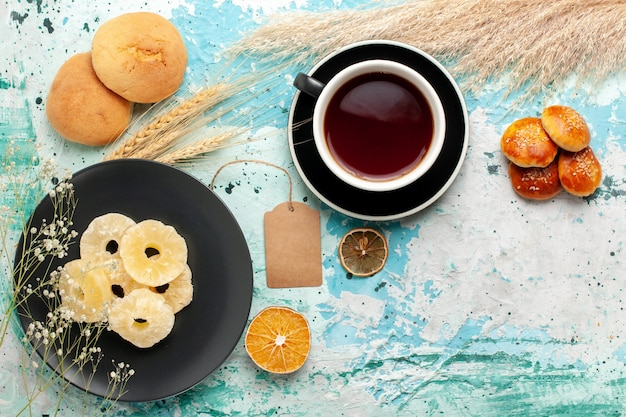 파란색 책상 케이크에 차 한잔과 함께 상위 뷰 말린 파인애플 링은 과일 비스킷 달콤한 설탕 쿠키를 구워