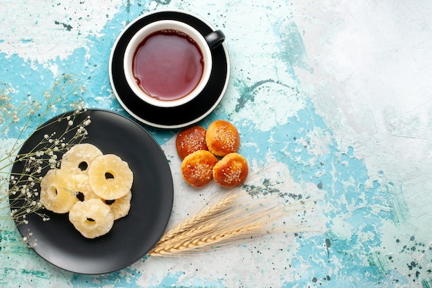 Top view dried pineapple rings with cup of tea and little cakes on blue background fruit pineapple dry sweet sugar