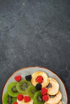 Anelli di ananas essiccati vista dall'alto con kiwi essiccati e mele sulla superficie grigio scuro