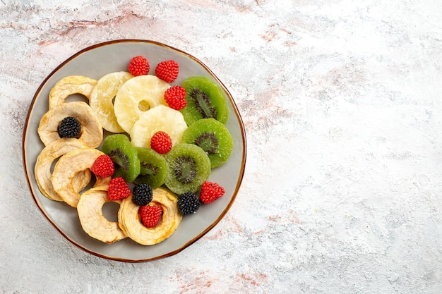 Anelli di ananas essiccati vista dall'alto con kiwi secchi e mele su superficie bianca