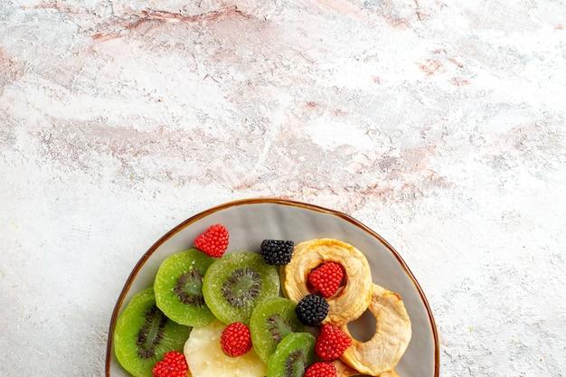 上面図乾燥したキウイのコンフィチュールと白い表面にリンゴが付いた乾燥パイナップルリング