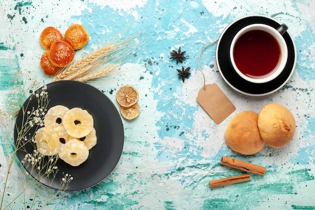 파란색 배경 케이크 빵 과일 비스킷 달콤한 설탕 쿠키에 작은 쿠키와 차 한잔 상위 뷰 말린 파인애플 링