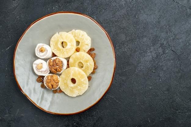 Anelli di ananas essiccati vista dall'alto con uvetta sulla superficie grigia