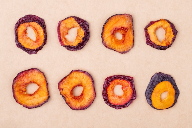 Top view of dried plum slices isolated on brown paper texture background