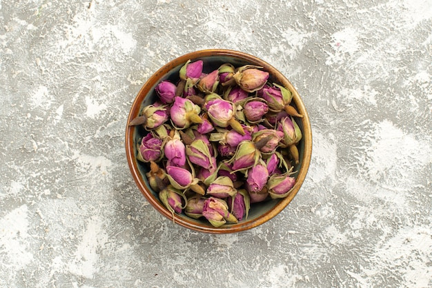 상위 뷰 흰색 배경에 접시 안에 보라색 꽃을 건조 꽃 식물 나무 색상