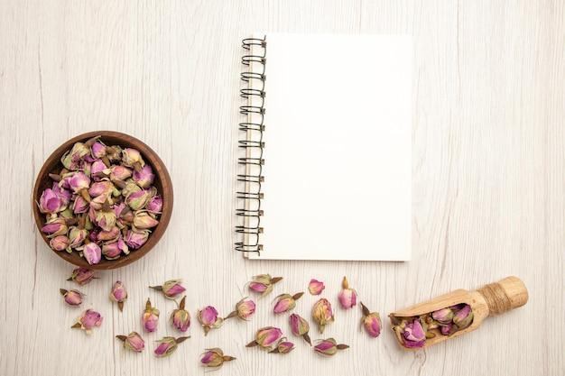 상위 뷰 흰색 책상 색상 꽃 보라색 카피 북에 메모장으로 보라색 꽃을 건조