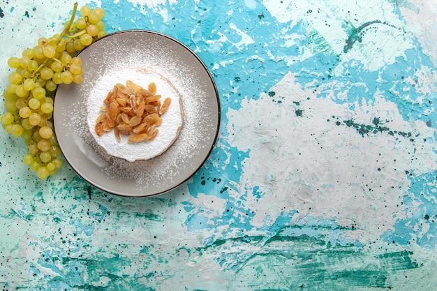 水色の机の上に新鮮な緑のブドウとブドウから乾燥レーズンの上面図