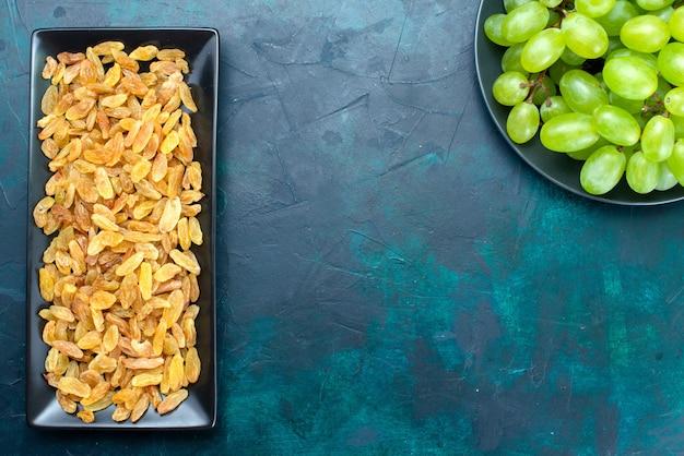 Vista dall'alto di uvetta essiccata all'interno del modulo nero con uva fresca verde sulla scrivania blu chiaro.