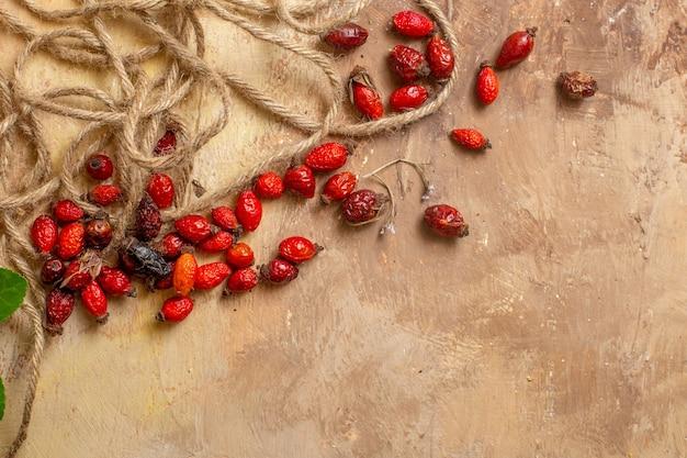 Вид сверху сушеных красных ягод с веревками на деревянном столе красные ягоды