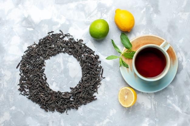 Вид сверху сушеный чай черного цвета, образующий круг с чаем и лимоном на светлом столе, зерновой чай сухого цвета