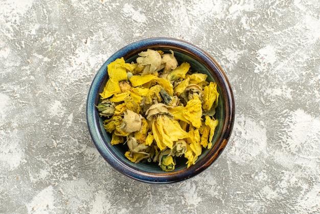 상위 뷰 흰색 배경에 접시 안에 노란색 꽃을 건조 꽃 식물 나무 색상