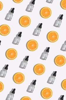 ビタミンc血清、化粧品オイル、白い背景のオレンジ色のスライスの上面ドロッパーボトル。物語のための垂直形式の創造的な化粧品パターン背景