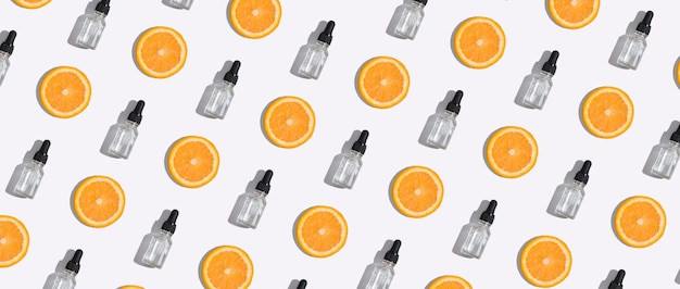 Top view dropper bottle of vitamin c serum, cosmetic oil and slices orange on white background. creative cosmetics pattern in banner format