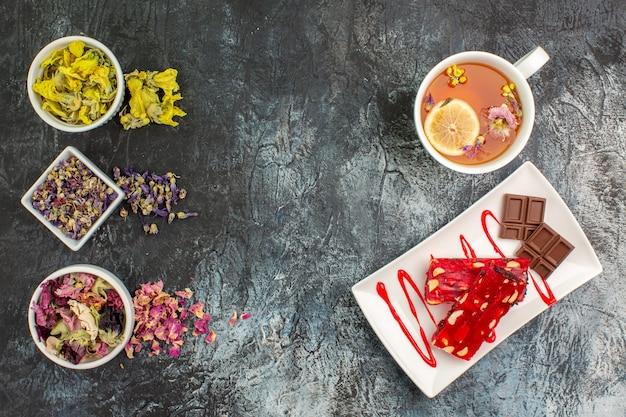Vista dall'alto di fiori secchi su ciotole e una tazza di tisana vicino a un piatto di cioccolato su fondo grigio