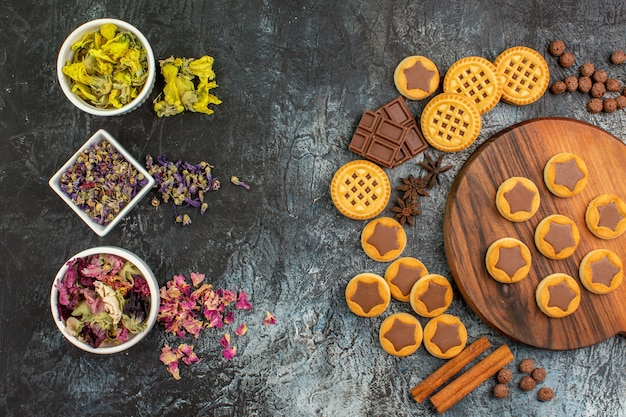 Top view of dry flowers on bowls with cookies on wooden platter and sweets on grey background