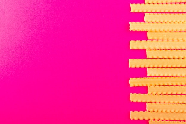 A top view dry italian pasta long raw lined on the pink