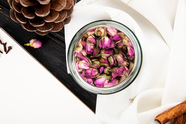 Vista superiore dei germogli rosa asciutti del tè in un barattolo di vetro su rustico