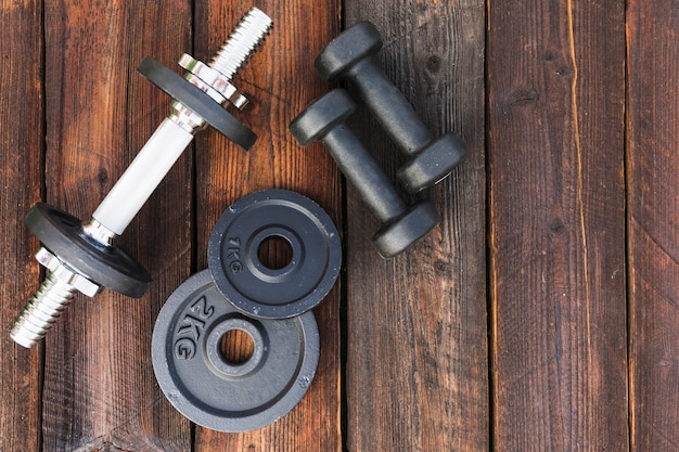 Top view of dumbbells and weight plates on wooden table