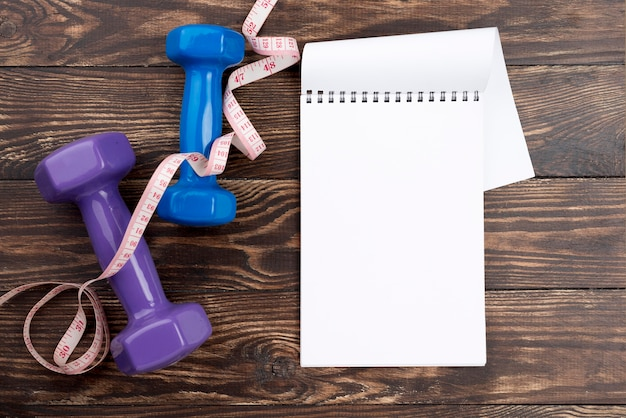 Top view dumbbells with notebook