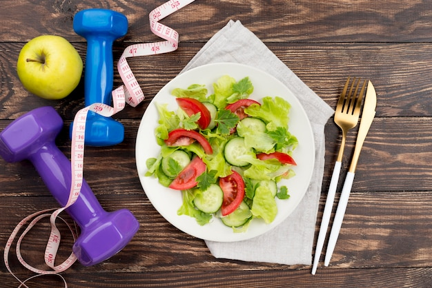 Top view dumbbells with salad