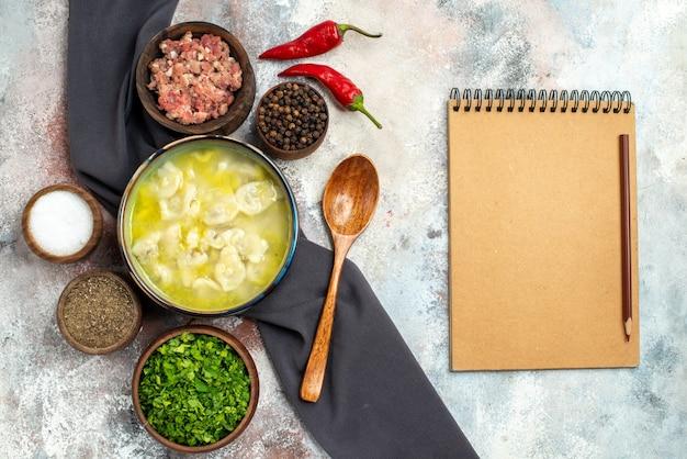 上面図dushbara黒のテーブルクロスボウルと肉の異なるスパイスグリーン木のスプーンのメモ帳ヌード表面
