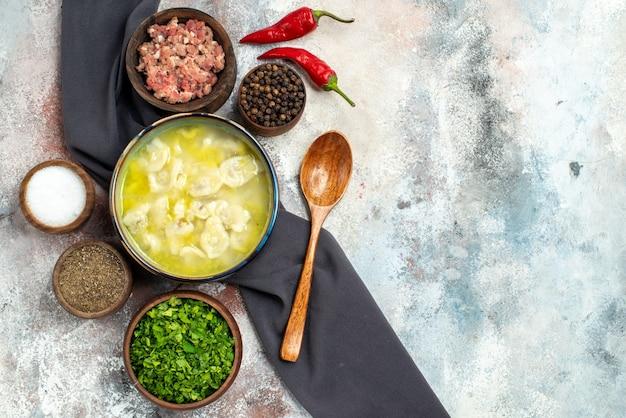 コピースペースで裸の表面に肉の異なるスパイス木のスプーンが付いている上面図dushbara黒いテーブルクロスボウル