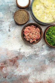 Ciotole dushbara vista dall'alto con diverse spezie verdi carne su spazio copia superficie nuda Foto Gratuite