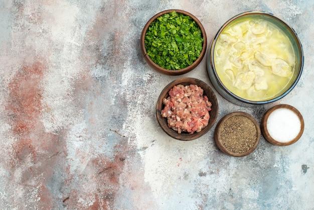 Ciotole di dushbara con vista dall'alto con diverse spezie e carne di verdure sul posto libero di superficie nuda Foto Gratuite