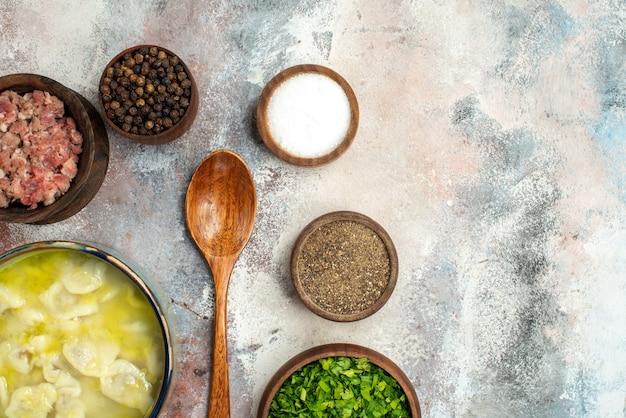 Ciotole dushbara vista dall'alto con diverse spezie verdi carne cucchiaio di legno su spazio libero superficie nuda