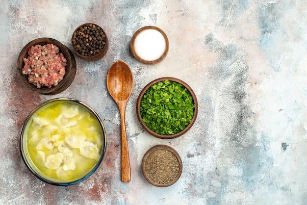 裸の表面の自由な場所の食べ物の写真にさまざまなスパイスグリーン肉木のスプーンで上面図dushbaraボウル