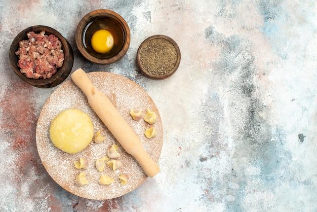 Vista dall'alto il mattarello della pasta dushbara sulla pasta spianatoia ciotole con il tuorlo d'uovo al pepe di carne sulla superficie nuda posto libero