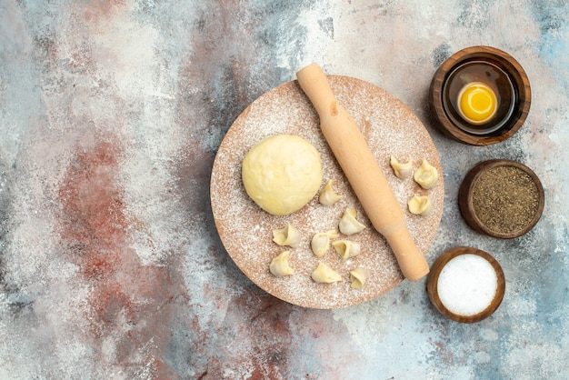 Vista dall'alto dushbara mattarello di pasta sulla spianatoia ciotole con sale, pepe e tuorlo d'uovo sulla superficie nuda