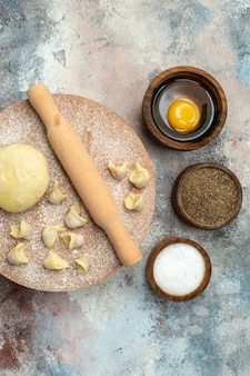 Vista dall'alto il mattarello di pasta dushbara sulla spianatoia ciotole con sale, pepe e tuorlo d'uovo sulla superficie nuda