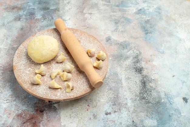 Vista dall'alto dushbara pasta mattarello sulla pasta spianatoia sulla superficie nuda cibo foto copia spazio