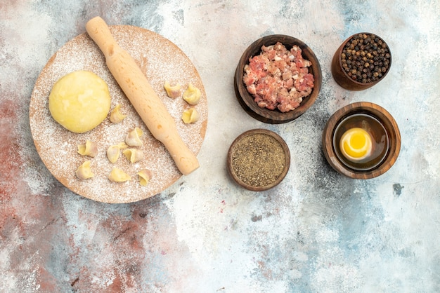복사 공간 누드 표면에 고기 후추 달걀 노른자와 반죽 과자 보드 그릇에 상위 뷰 dushbara 반죽 롤링 핀