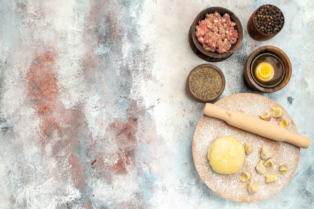 무료 장소와 누드 표면에 고기 후추 달걀 노른자와 반죽 과자 보드 그릇에 상위 뷰 dushbara 반죽 롤링 핀
