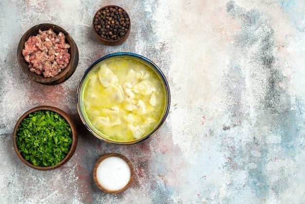 裸の表面のコピースペースにミートグリーンペッパーソルトとトップビューのdushbara餃子スープボウル