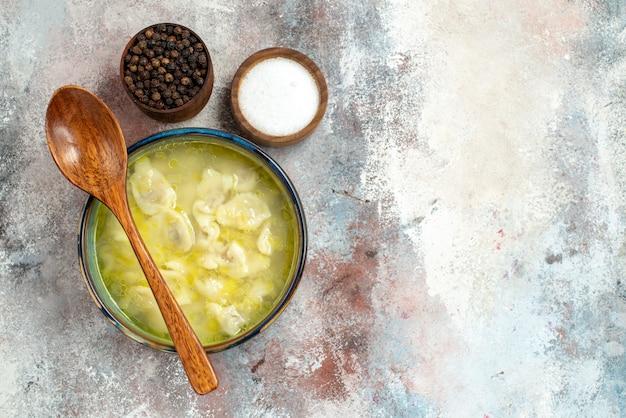 Vista dall'alto gnocchi di dushbara ciotole di zuppa con sale pepe cucchiaio di legno sulla ciotola sulla superficie nuda posto libero piatto azerbaigiano