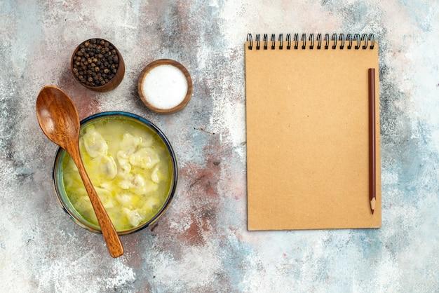 누드 표면에 노트북과 연필 그릇에 소금 후추 나무 숟가락으로 상위 뷰 dushbara 만두 수프 그릇
